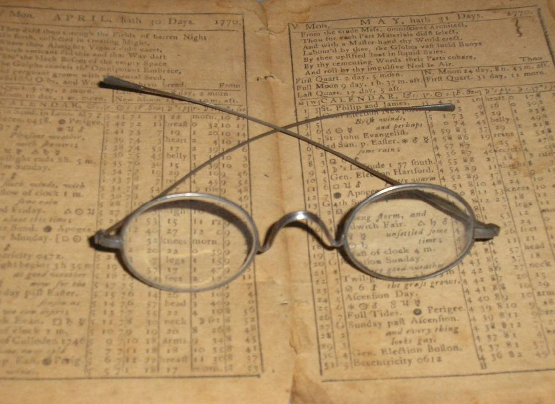 Antique eyeglasses resting on an 18th century almanack.