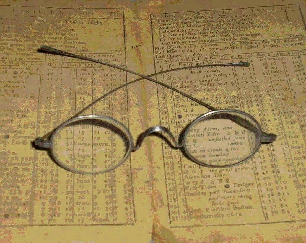 Antique eyeglasses resting on an opened 18th century almanack.